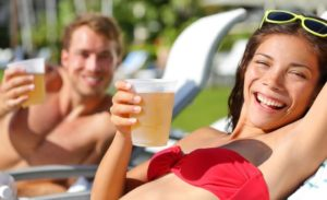 man and woman smiling on lounge chairs while holding beers